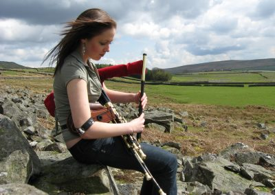 Catherine ashcroft outdoors with uilleann pipes